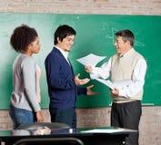 Professor Giving Test Result till den manliga studenten At Arkivbild