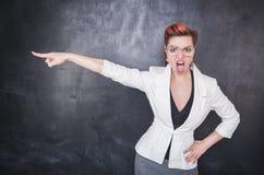 Professor gritando irritado que indica no fundo do quadro-negro imagem de stock royalty free