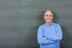 Professor With Hands Folded Standing Against Chalkboard Stock Images