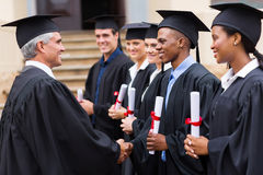 Professor handshaking graduates Stock Image