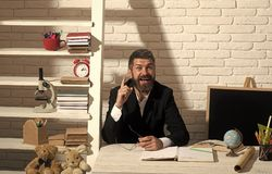 Professor with happy face having idea. Teacher and school supplies. In classroom. Man with beard on white brick wall background. Education and knowledge concept royalty free stock photos