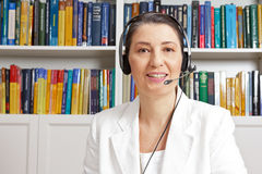 Professor headset microphone distance university. Friendly middle aged woman with headphones and white blazer in front of a bookshelf in her study, having a live Stock Photos