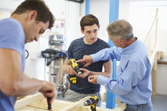 Professor Helping College Student que estuda a carpintaria imagem de stock