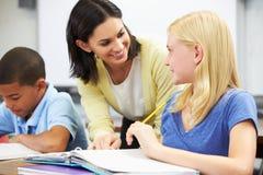 Professor Helping Pupils Studying em mesas na sala de aula fotografia de stock