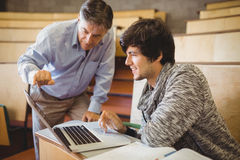 Professor helping a student in classroom. At college stock photo