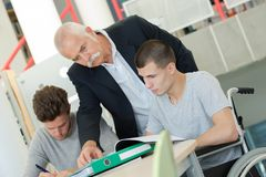 Professor helping young disabled student at library Royalty Free Stock Photos