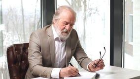 Professor idoso com cabelo e a barba cinzentos no terno bonito que toma notas no caderno filme