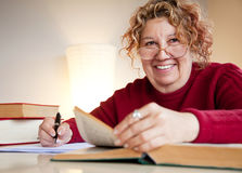 Professor over books smiling. Mature female is sitting by a table with books and a pen, smiling Stock Photos