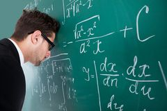 Professor leaning head on blackboard. Side view of sad young male professor leaning head on blackboard in classroom royalty free stock photography