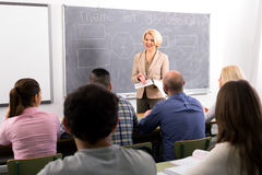 Professor lecturing students. Female professor standing in front of students and lecturing them royalty free stock image