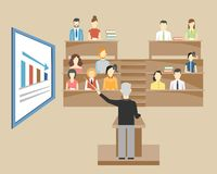 Professor lecturing to students at university. Professor standing in the front of the class at a lectern lecturing to students at university who are sitting in Royalty Free Stock Image