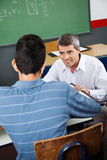 Professor Looking At Male High School Student. Mature professor looking at male high school student at desk in classroom Stock Image