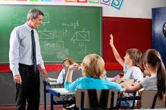 Professor Looking At Schoolboy Raising Hand. Happy mature professor looking at little schoolboy raising hand in classroom Royalty Free Stock Photography