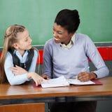 Professor Looking At Schoolgirl bij Bureau stock afbeelding