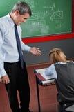 Professor Looking At Schoolgirl In Classroom stock photos