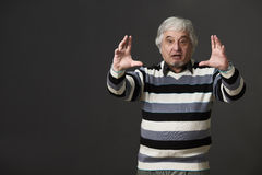 Professor man of university or colleage in studio. Professor man of university or colleage giving two hands while explaining new material to students or pupils Royalty Free Stock Images