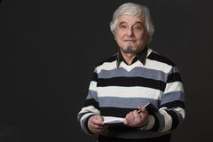Professor man of university or colleage in studio. Portrait of professor man of university or colleage holding book or notebook in front of him and looking at Royalty Free Stock Photography