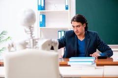 Professor masculino e estudante de esqueleto na sala de aula imagens de stock