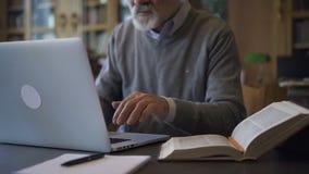 Professor masculino maduro no livro de leitura redondo dos vidros video estoque