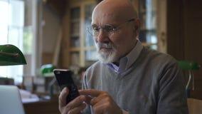 Professor masculino maduro nos vidros redondos que surfam o Internet video estoque