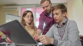 Professor masculino maduro que ajuda seus estudantes com atribuição, usando o portátil filme