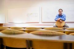 Professor masculino que senta-se na cadeira no salão de leitura fotos de stock