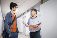 Professor med anteckningsboken som talar till en student royaltyfria foton