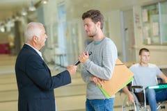Professor med anteckningsboken som talar till studenten i korridor fotografering för bildbyråer