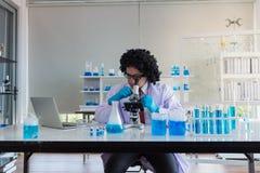 Professor mit dem gelockten Haar, das im Forschungszentrum unter Verwendung eines Mikroskops arbeitet Chemiker, die mit blauen Fl stockfotos