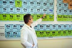Professor na classe com a tabela periódica dos elementos Fotografia de Stock Royalty Free