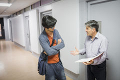 Professor with notebook talking to student. In corridor Royalty Free Stock Photography