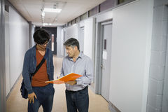 Professor with notebook talking to a student Stock Image