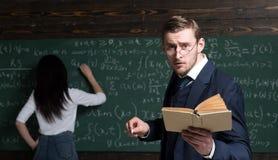Professor novo agitado com o olhar ansioso que está na sala de aula com livro e no giz em suas mãos Estudante novo fotografia de stock