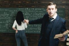Professor novo agitado que aponta na placa verde com muita escrita feita pelo estudante fêmea na ligação em ponte e no azul branc foto de stock