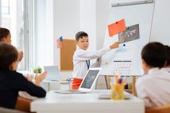 Professor novo que ensina outras crianças em uma sala de aula imagem de stock