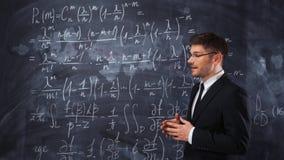 Professor ou estudante do homem novo que explicam a decisão da equação dura da matemática vídeos de arquivo