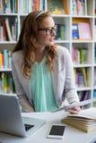 Professor pensativo que usa a tabuleta digital com portátil e telefone na tabela na biblioteca fotografia de stock