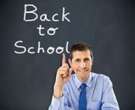 Professor pointing back to school. Male teacher smiling by blackboard. male teaching writing BACK TO SCHOOL on chalkboard.Male primary school teacher Stock Photos