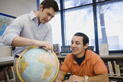 Professor Pointing Out Location On Globe To Student Stock Photo