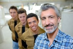 Professor posing with vocational students. Professor royalty free stock image