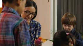 Professor pré-escolar bonito que trabalha com crianças diversas filme