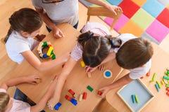 Professor pré-escolar com as crianças que jogam com os brinquedos didáticos de madeira coloridos no jardim de infância imagem de stock royalty free