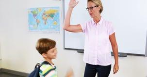 Professor primário e crianças que dão a elevação cinco na sala de aula