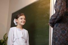 Professor primário feliz que ajuda uma estudante que faz uma adição em um quadro-negro imagens de stock