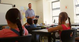 Professor primário masculino caucasiano que usa a tabuleta digital ao ensinar na sala de aula 4k vídeos de arquivo