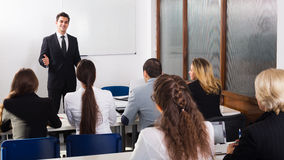 Professor and professionals at courses. Happy young professor and professionals at extension business courses stock images