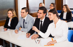 Professor and professionals at courses. Professor and positive professionals at extension business courses indoors stock image