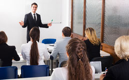 Professor and professionals at courses. Smiling adult professor and professionals at extension business courses royalty free stock photography