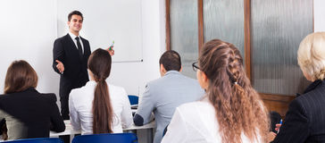 Professor and professionals at courses. Smiling professor and professionals at extension business courses stock images