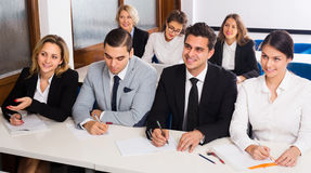 Professor and professionals at courses. Professor and smiling professionals at extension business courses indoors royalty free stock photography